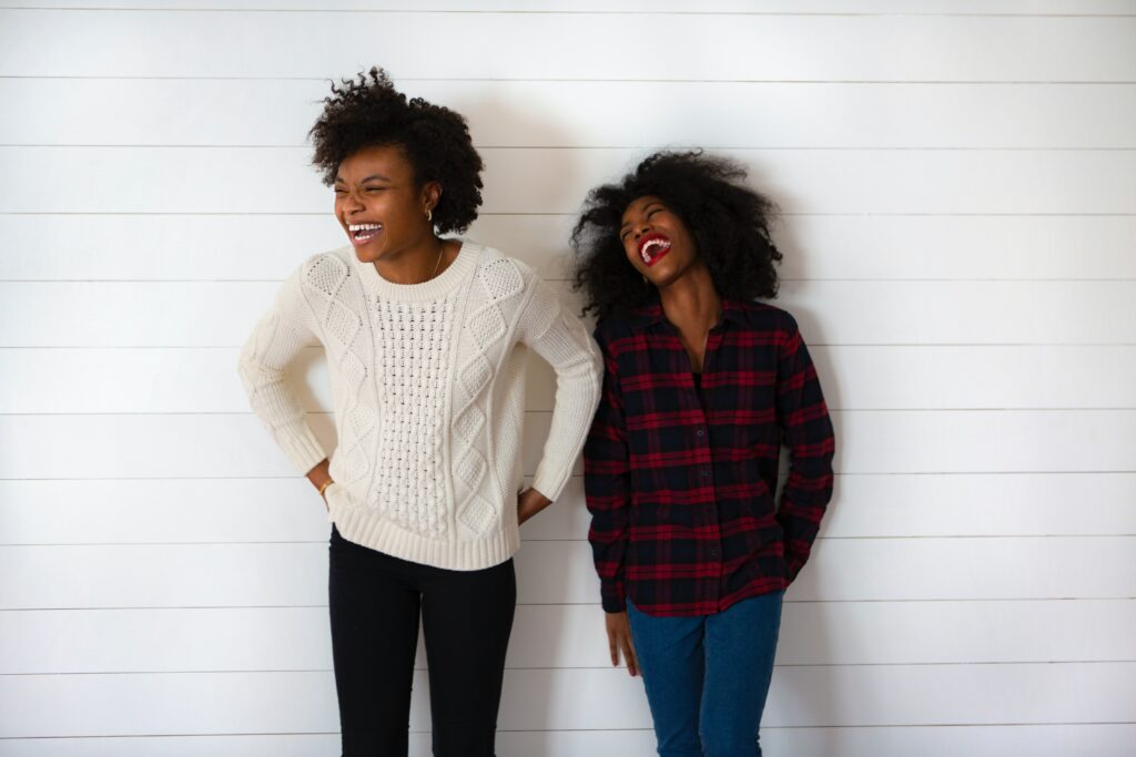 Two women with afro hair, smiling and laughing against a wall