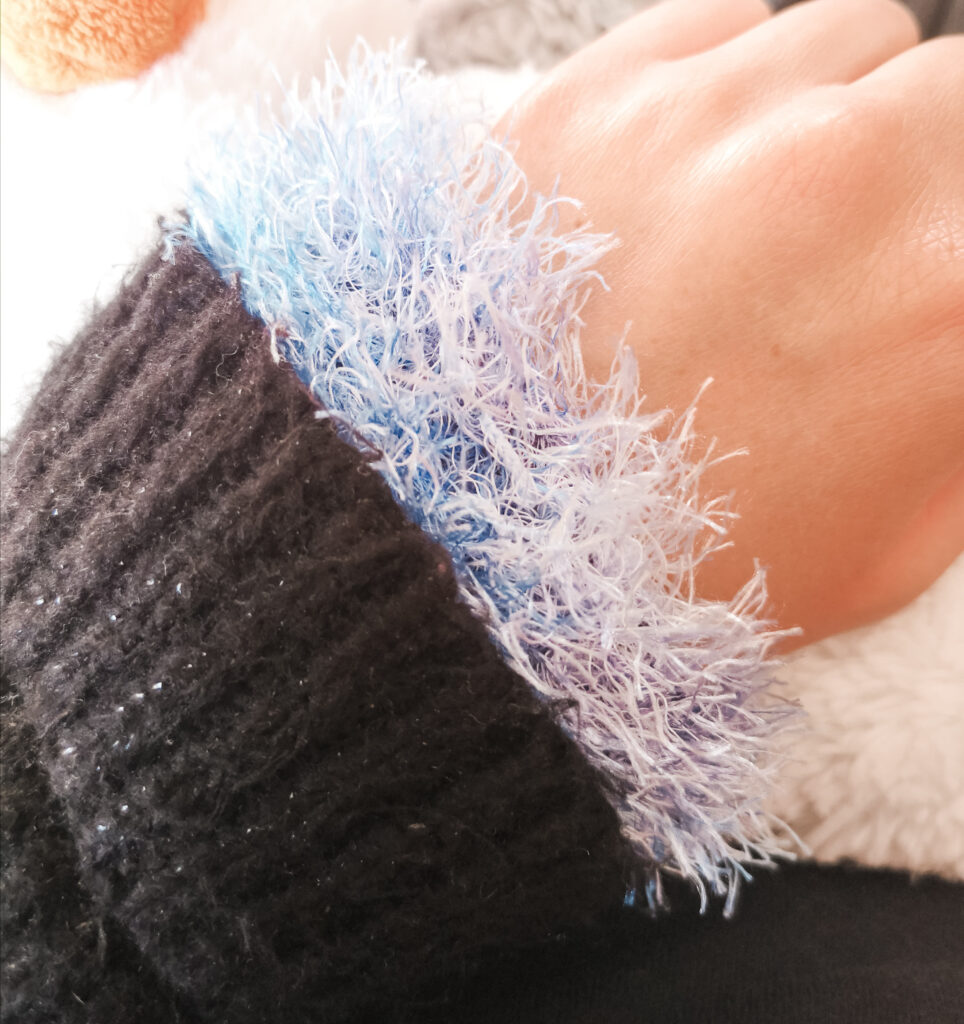 Light blue knitted wrist warmer on my wrist, tucked into the sleeve of my black jumper.