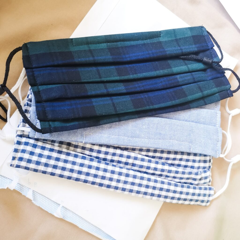 Three handmade face masks - one tartan, one light blue and one blue gingham.