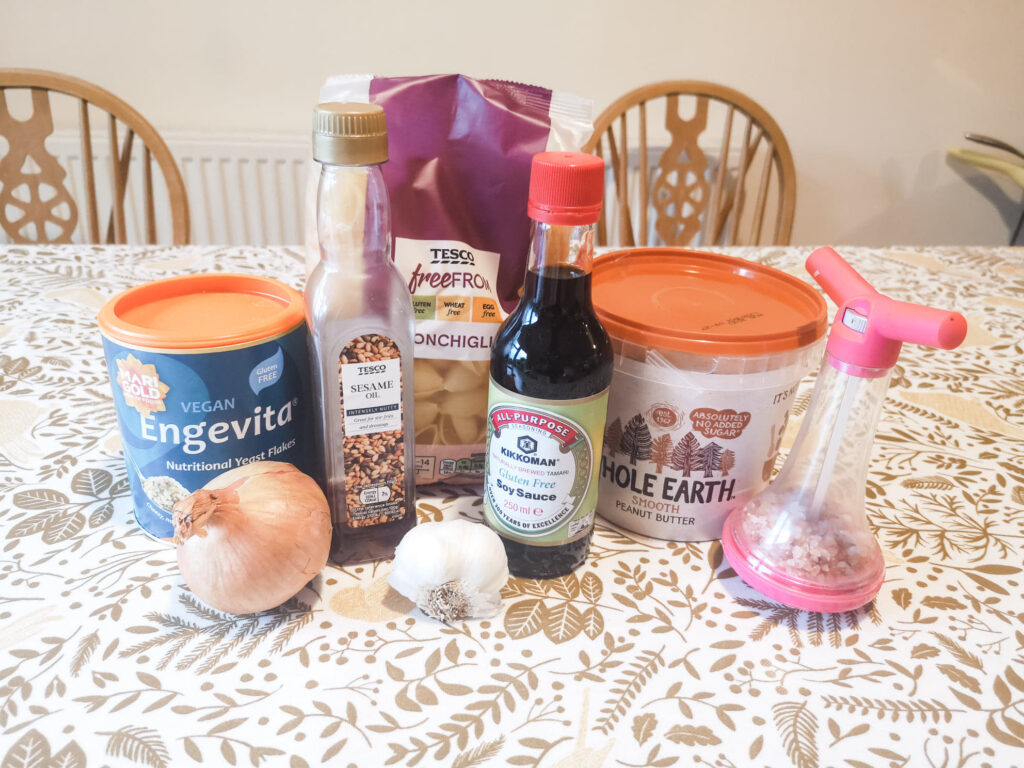 The ingredients for peanut butter pasta laid out on a table: pasta, peanut butter, soy sauce, sesame oil, nutritional yeast, onion, garlic and salt.