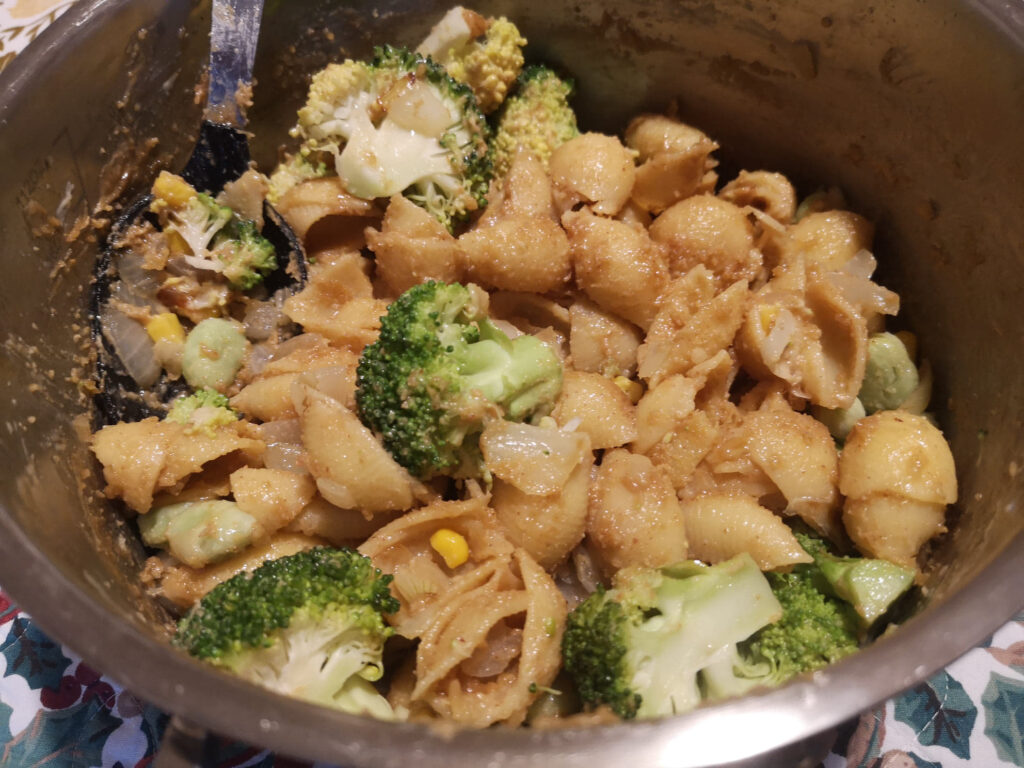 Peanut butter pasta with broccoli and sweetcorn in a saucepan.