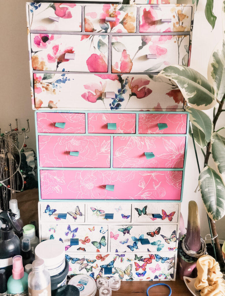 3 colourful sets of mini drawers, stacked on top of each other. The drawers have floral and butterfly patterns on them. They are surrounded by beauty products and a houseplant.