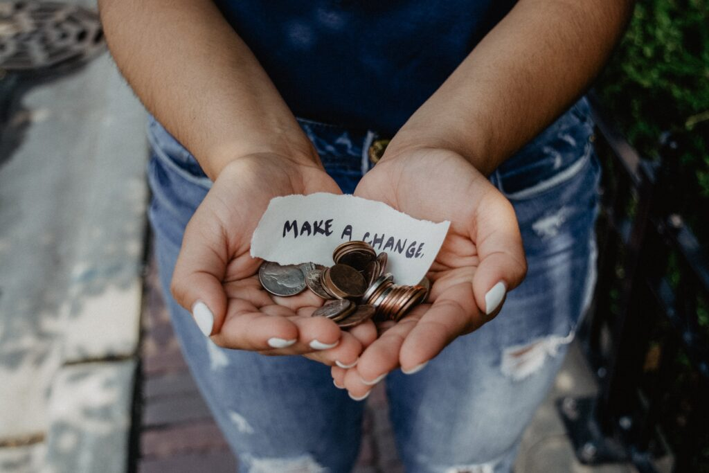 A pair of cupped hands holding coins and a piece of paper saying 'make a change'.