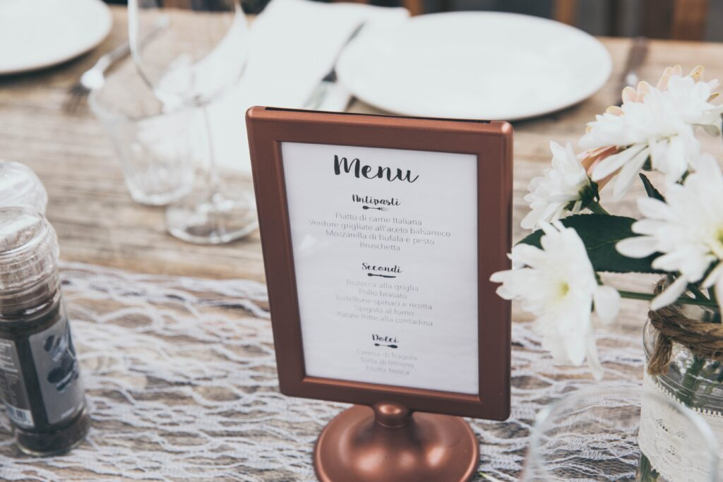 A menu on a table, that has been set ready for a meal, with a jar of flowers.