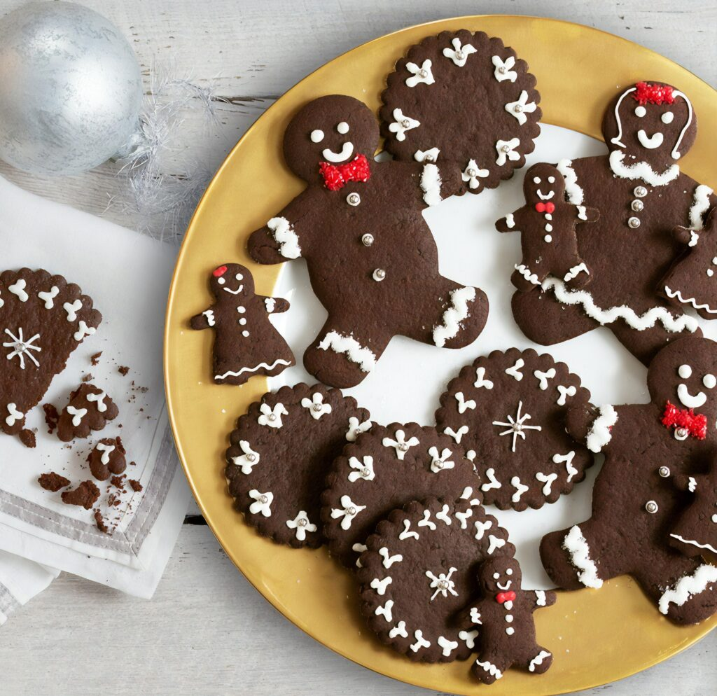 A plate of chocolate gingerbread men and cookies.
