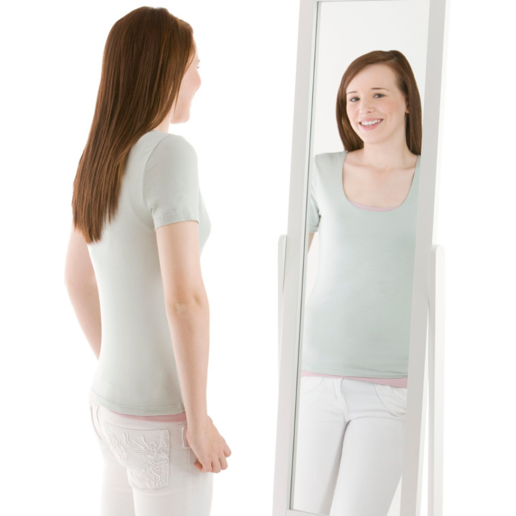 A woman wearing a pale green top and white trousers looking at herself in a mirror and smiling.