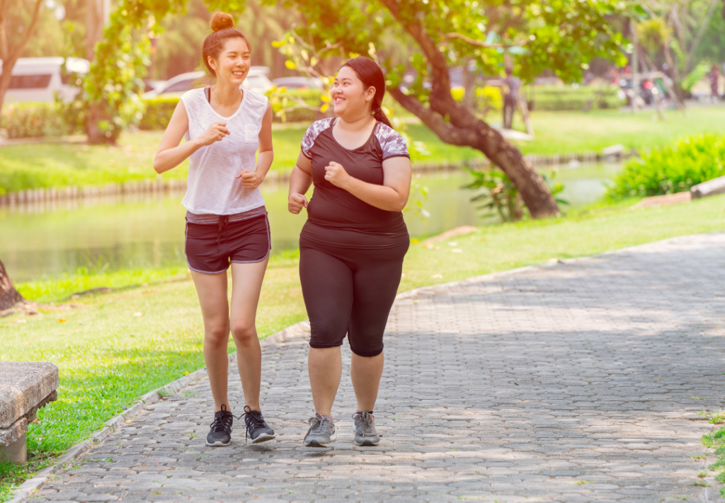 Two women running together in a park and smiling.