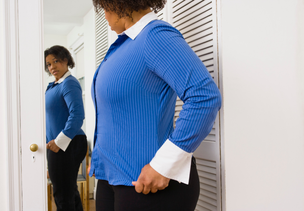 A woman wearing a blue shirt and black trousers is looking at herself in the mirror and she looks worried.
