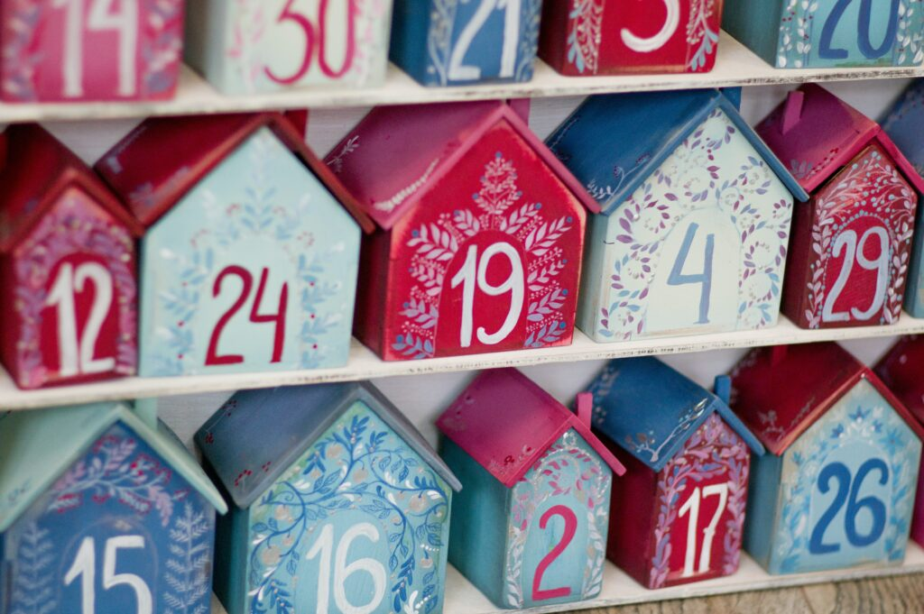 An advent calendar made up of little wooden houses painted red and blue with numbers on.