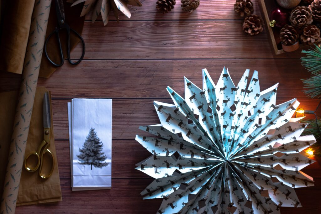 Paper Christmas decorations, scissors, wrapping paper and pinecones.