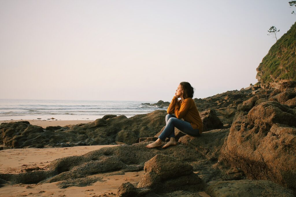 A woman wearing an orange top and blue jeans, sitting on a rock on the beach, looking thoughtful.