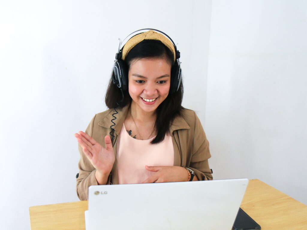 A woman wearing headphones and waving at her laptop during a video call.