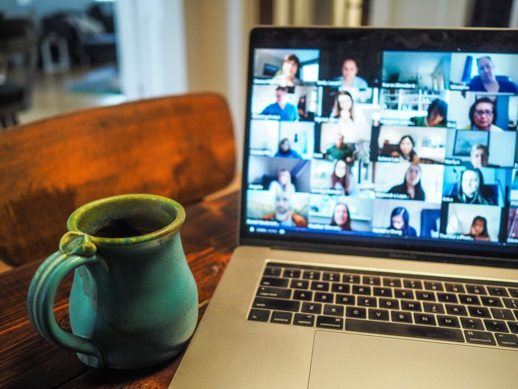 A laptop screen with a group video call occurring - many faces are on the screen. There is a green mug next to the laptop.