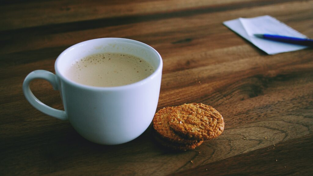 A cup of coffee and three biscuits on a desk, along with a piece of paper and a pen.