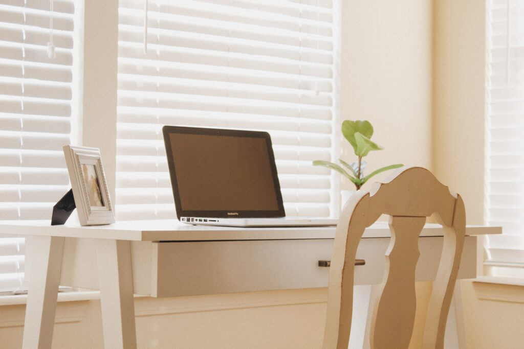 A tidy desk with a laptop, plant and framed photo on it.