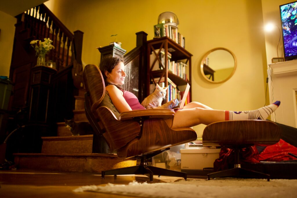 A woman sitting back in a chair with her feet up on a footstool. She has a laptop on her lap and a cat beside her looking at the screen.