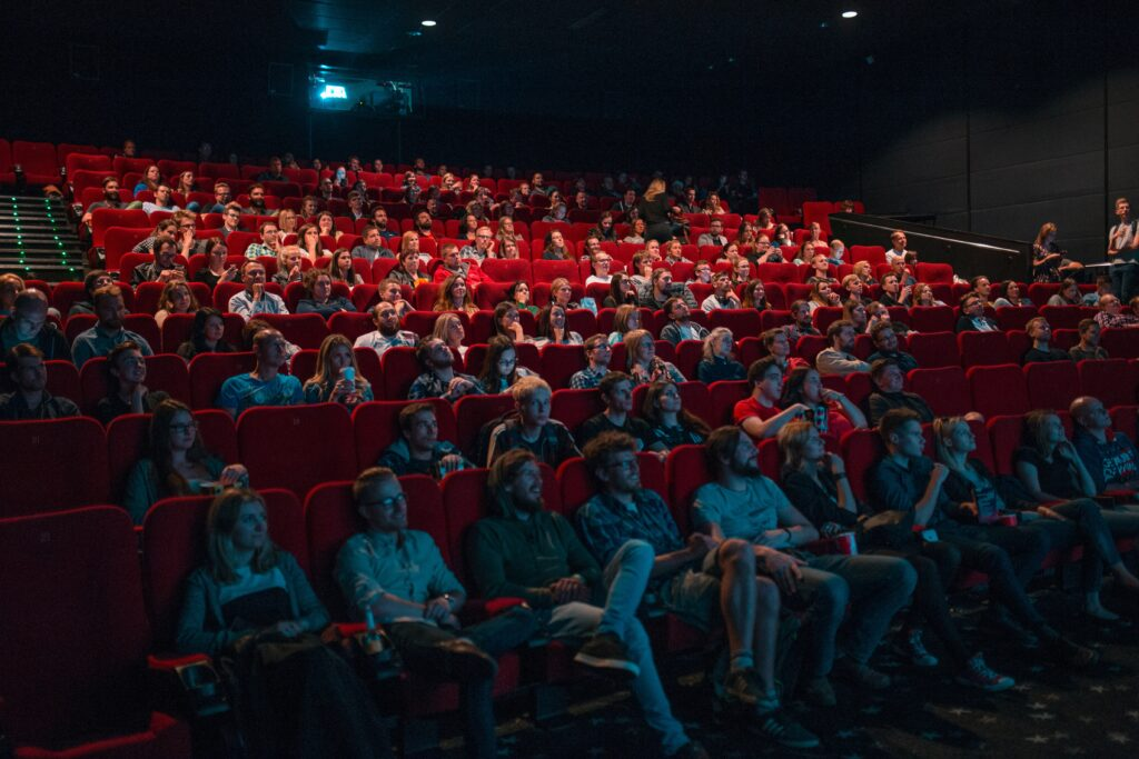 An audience in a theatre watching a show. The chairs are red and the theatre is about two-thirds full.