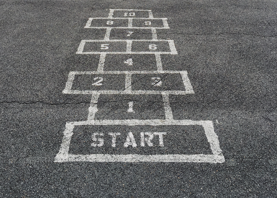 A hopscotch painted on tarmac, with numbers 1 to 10.