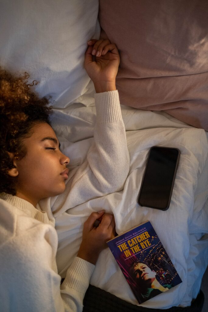 A woman asleep in bed with a phone and a book next to her.