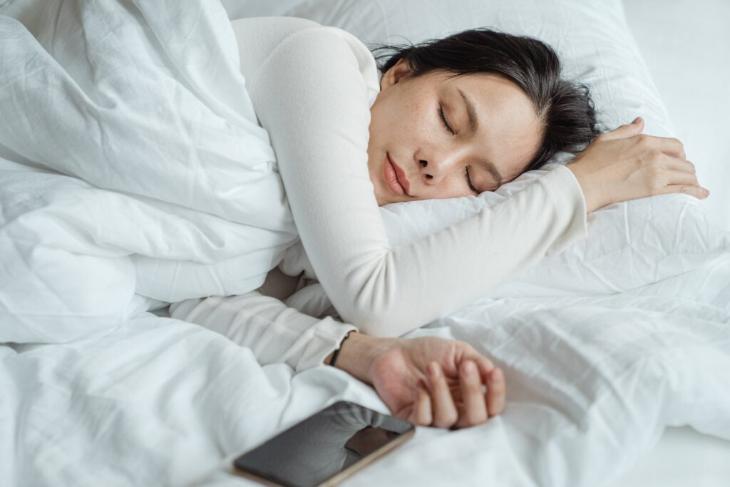A woman asleep in bed with her phone laying next to her outstretched hand.