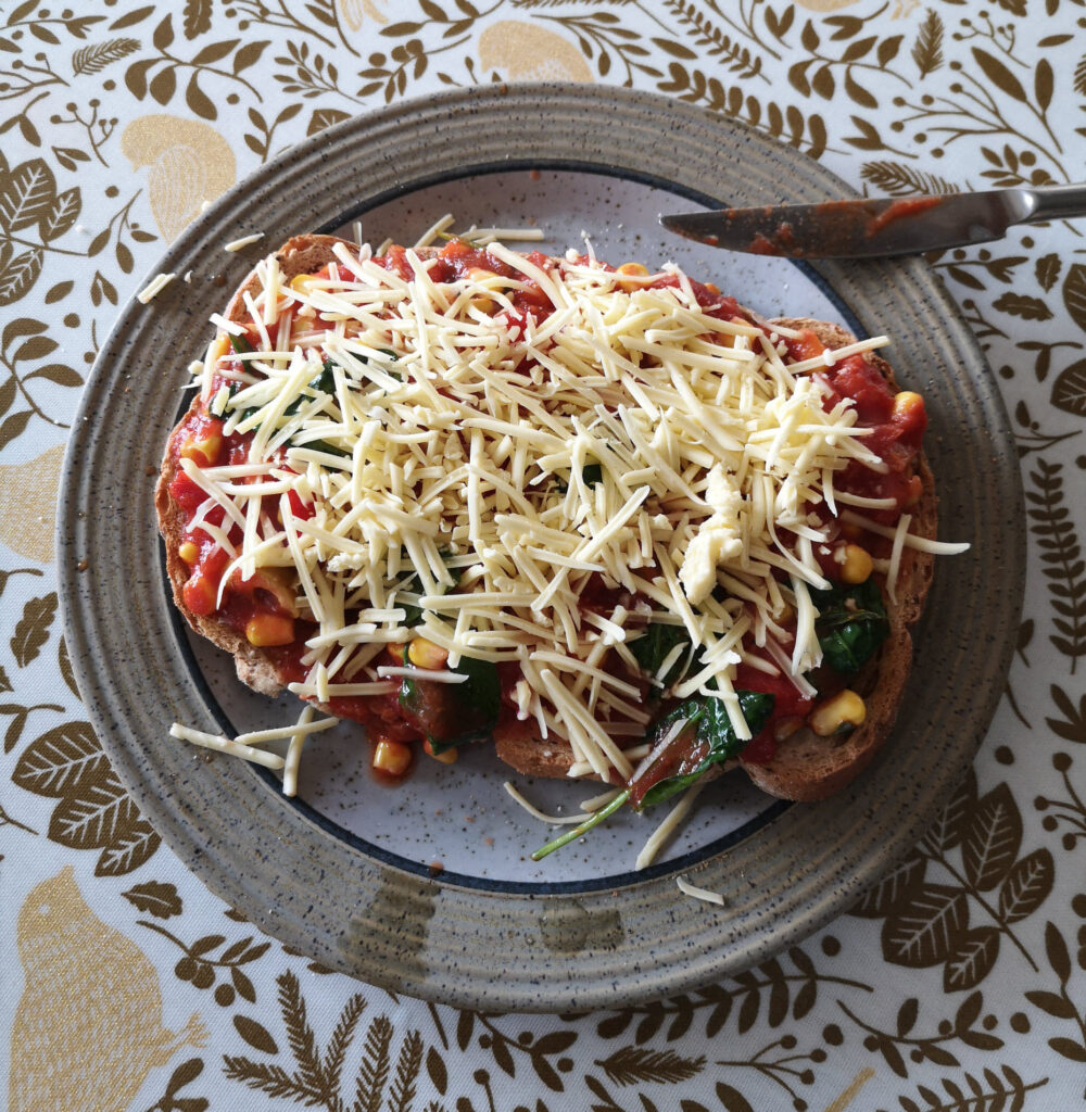 A mini toast pizza on a plate, topped with tomato sauce, vegetables and cheese.