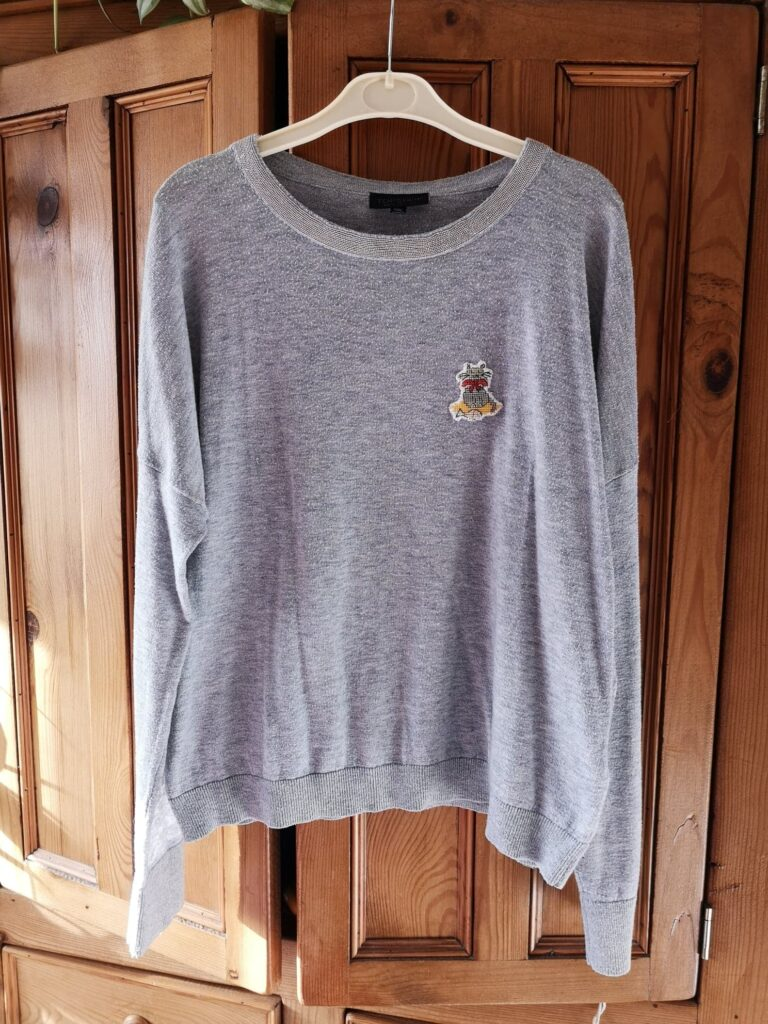 A grey jumper with a cat cross-stitch sewn onto the front of it.