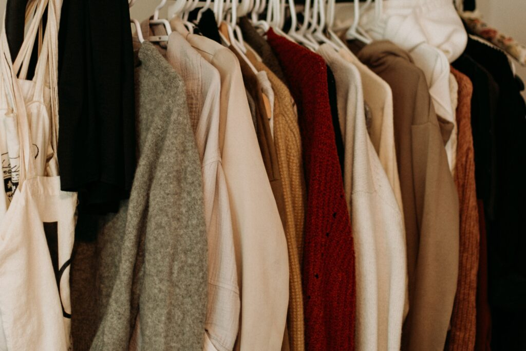 A rail of clothes in neutral colours including cream, brown and orange.