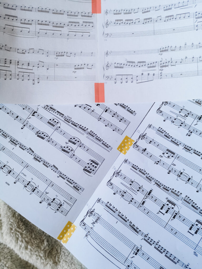 Several pages of sheet music that have been stuck together with pink and yellow washi tape.