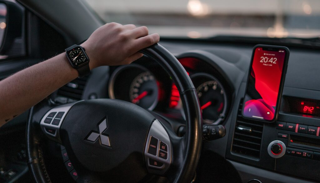 A car dashboard showing the car clock, a mounted smartphone, and a hand on the steering wheel wearing a wristwatch.