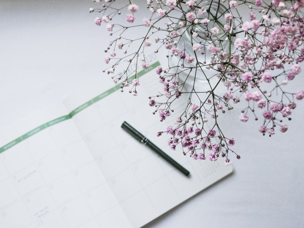 A planner and pen with a vase of delicate pink flowers next to it.