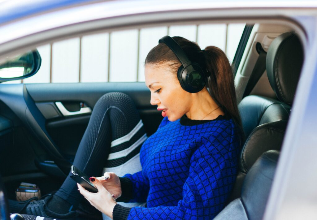 A woman sitting in a parked car with one foot up on the seat. She is wearing headphones and looking at her phone.