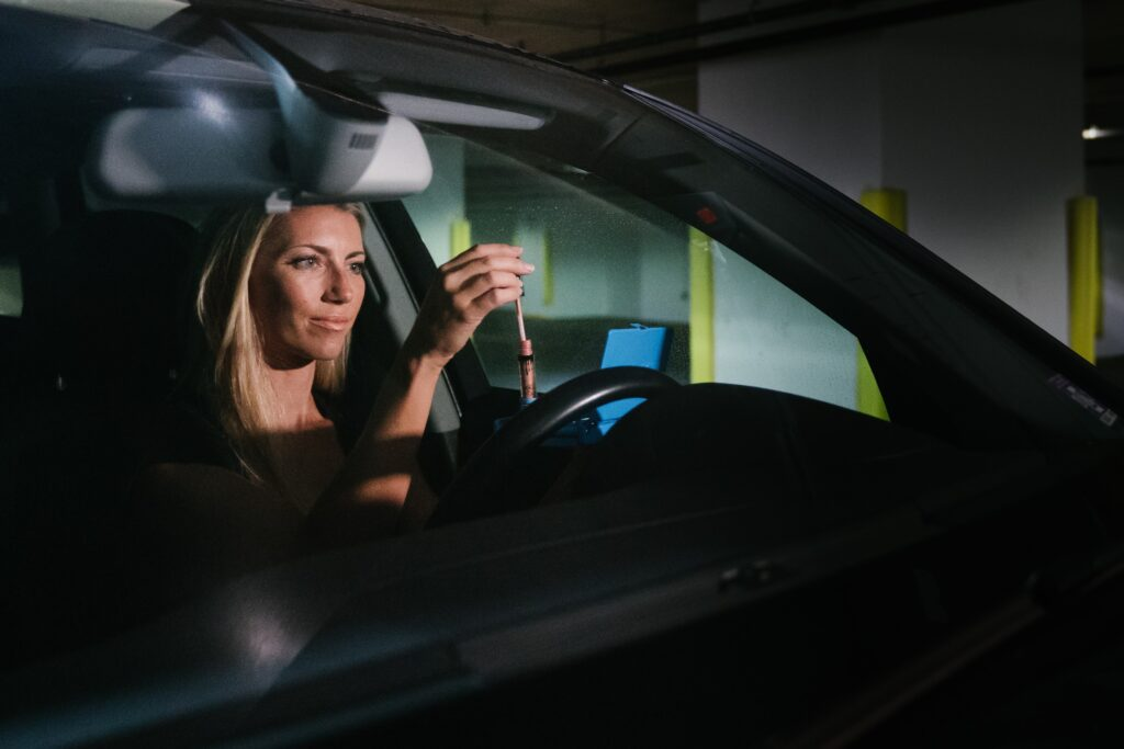A woman applying lip gloss in a car.