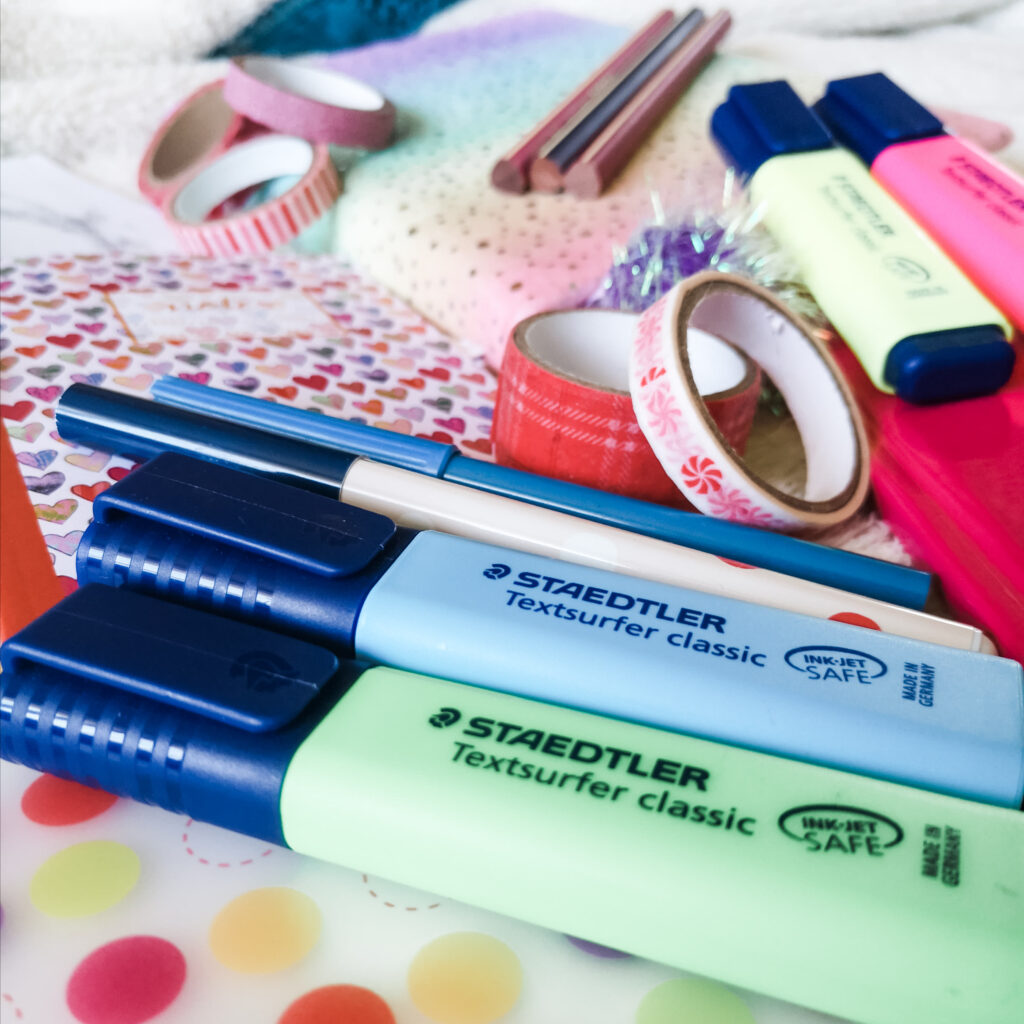 A selection of colourful stationery including notebooks, highlighter pens, washi tape, colouring pencils and pens.