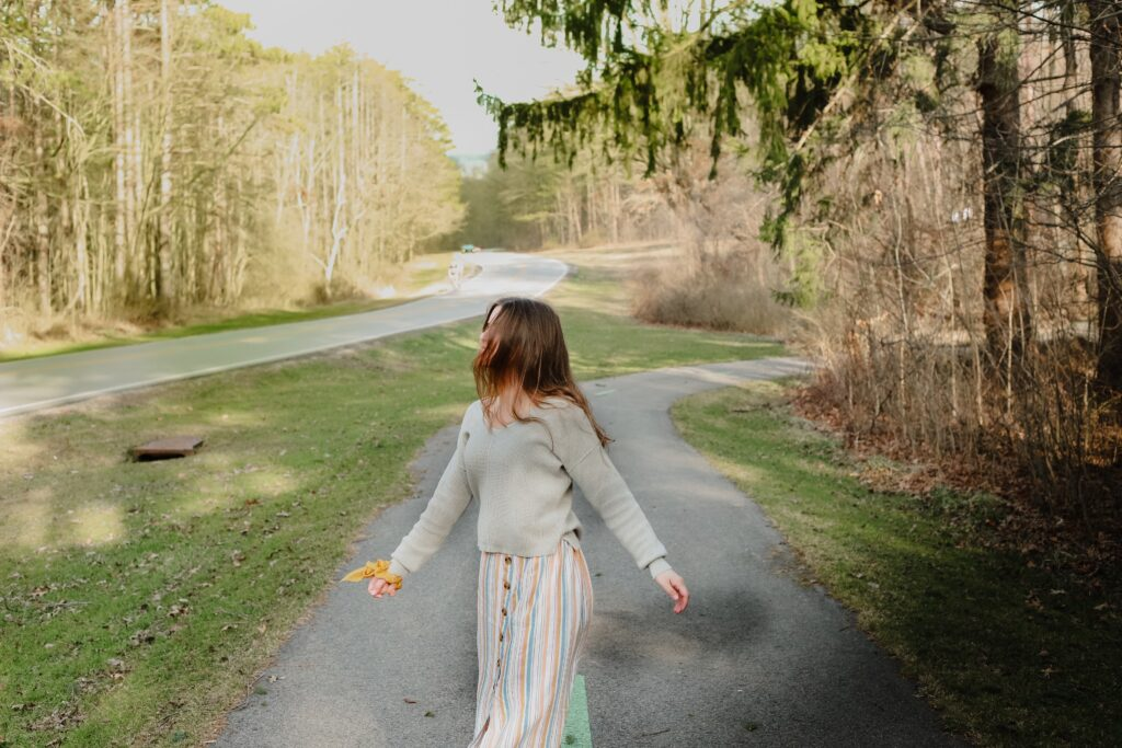 A woman walking along a path surrounded by grass and trees. She looks happy and is holding her arms slightly raised.