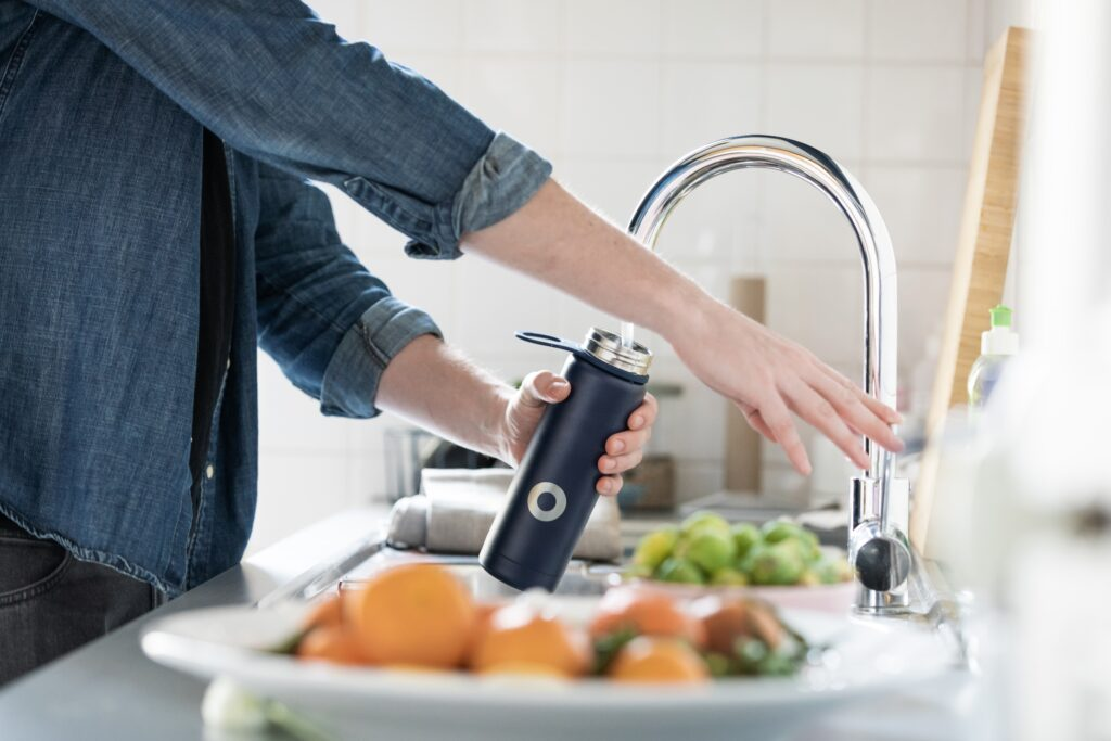 A person filling up a black water bottle from a kitchen tap.