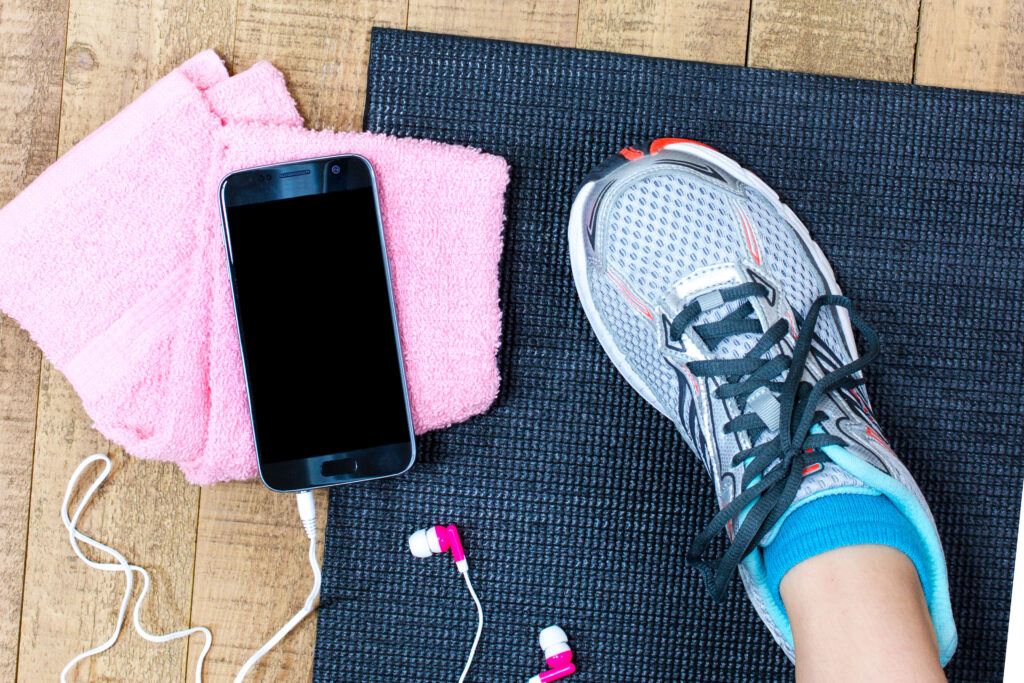 A flatlay of a foot in a trainer, a phone, earbuds, a flannel and a yoga mat.