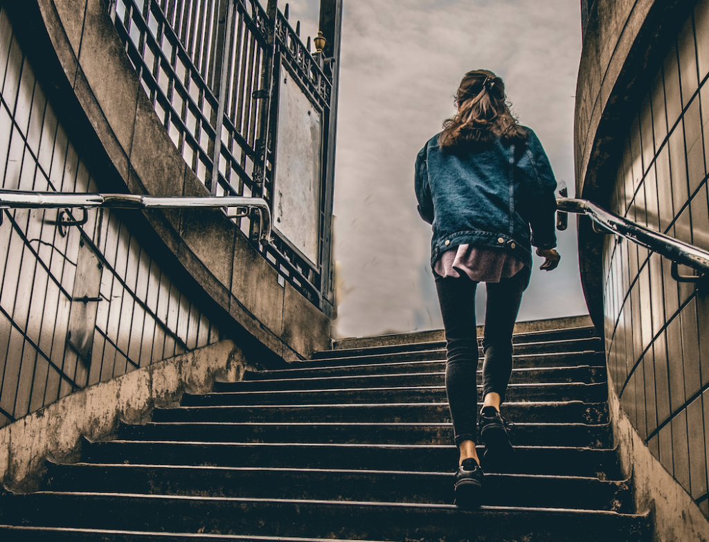 A woman walking up a flight of stairs.