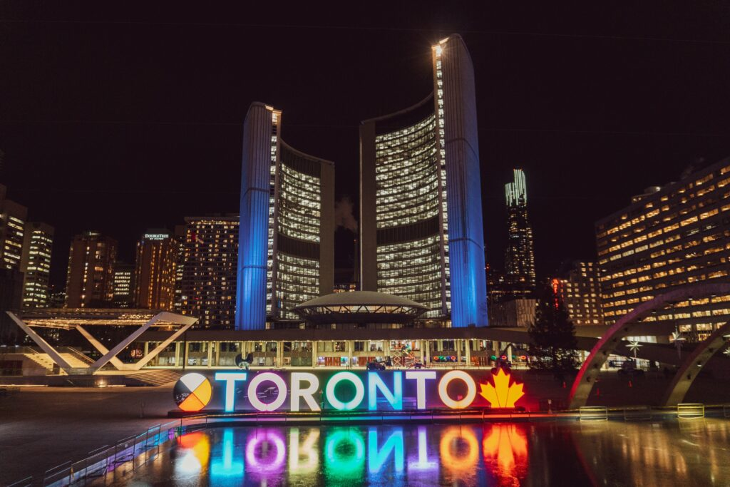 A view of Toronto at night time, featuring a lit up Toronto sign reflecting in the water, with buildings in the background.