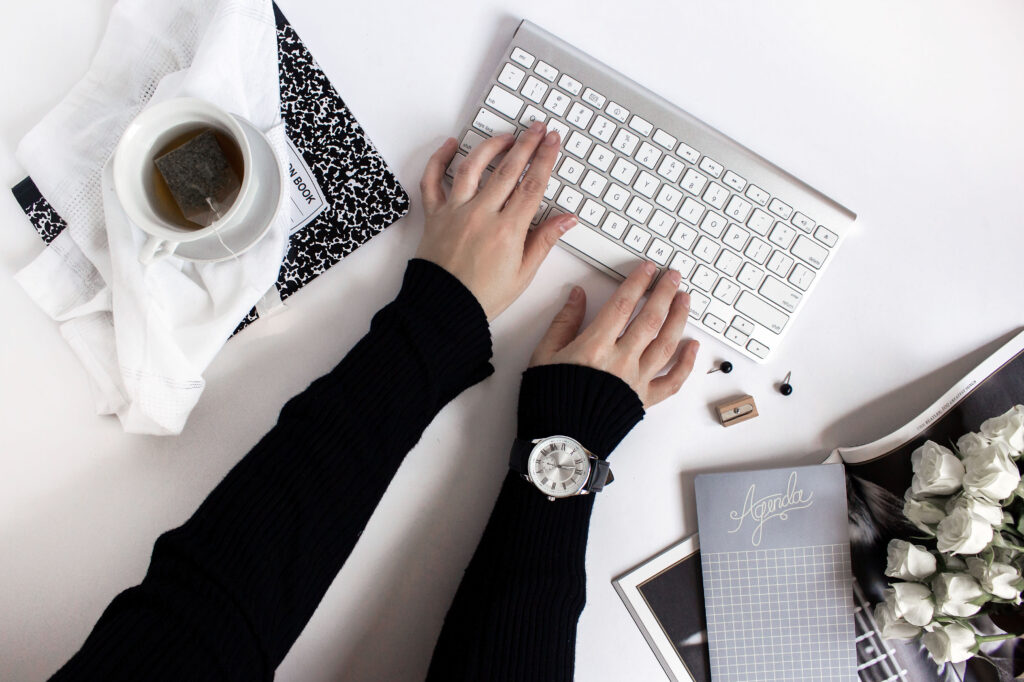 A flatlay of a pair of hands typing on a wireless keyboard. The arms are wearing black sleeves, and there is a cup of tea and various stationery items surrounding the arms and keyboard.