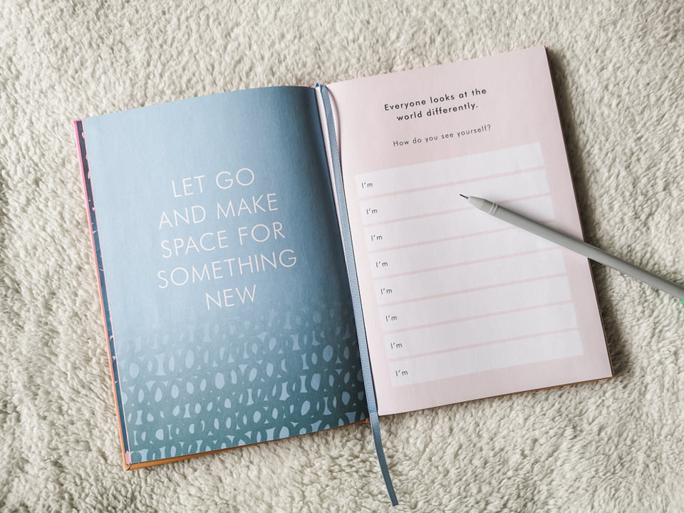 An open journal, with a quote saying 'let go and make space for something new' on the left hand page, and boxes to fill in on the right hand page. There is a grey pen resting on the journal.