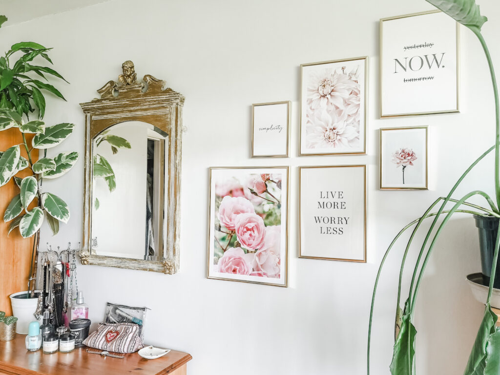 My bedroom wall with floral and quote posters hanging on it, as well as a mirror. Houseplants and a dresser are visible too.