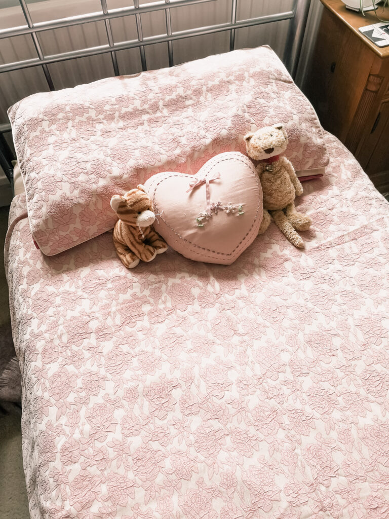 A bed with pink floral duvet cover and pillow. There is a pink, heart-shaped cushion on the bed as well as two cat soft toys.