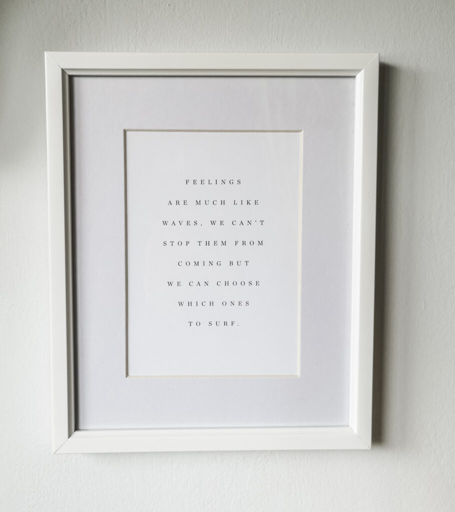 A poster reading 'Feelings are much like waves, we can't stop them from coming but we can choose which ones to surf.' in a white frame on a white wall.