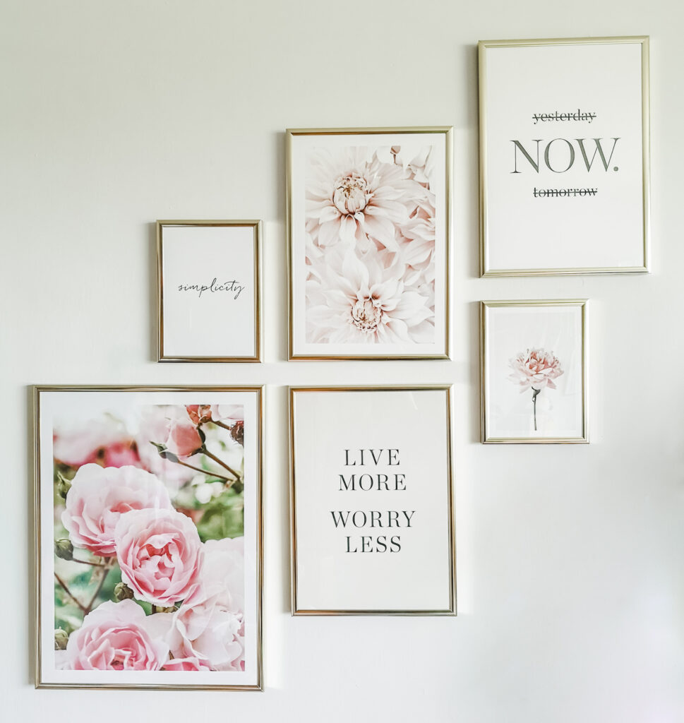Six posters hanging on a white wall. Three of them have quotes, and three feature pink flowers. They are all in gold frames.