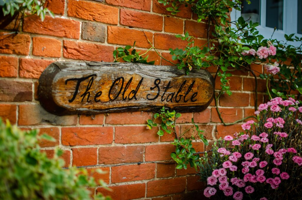 A house name sign reading The Old Stable, on an old piece of wood.