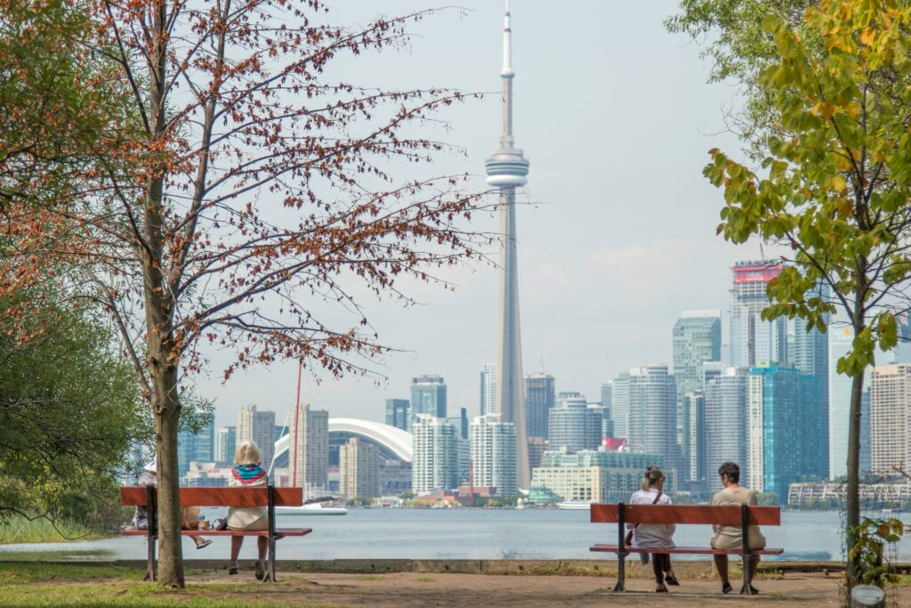 People sitting on benches on Toronto Island, with a view across the water to the Toronto skyline including the CN Tower.