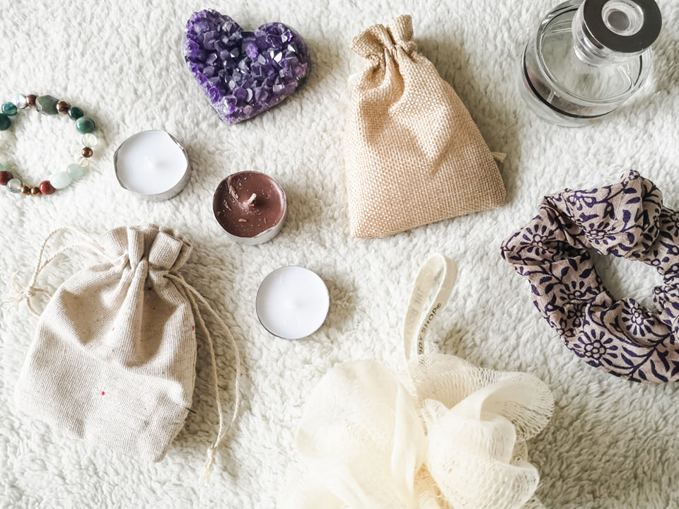 A flatlay of various self-care items including candles, bath salts, a loofah, a bracelet, a scrunchie, a crystal heart and a bottle of perfume.