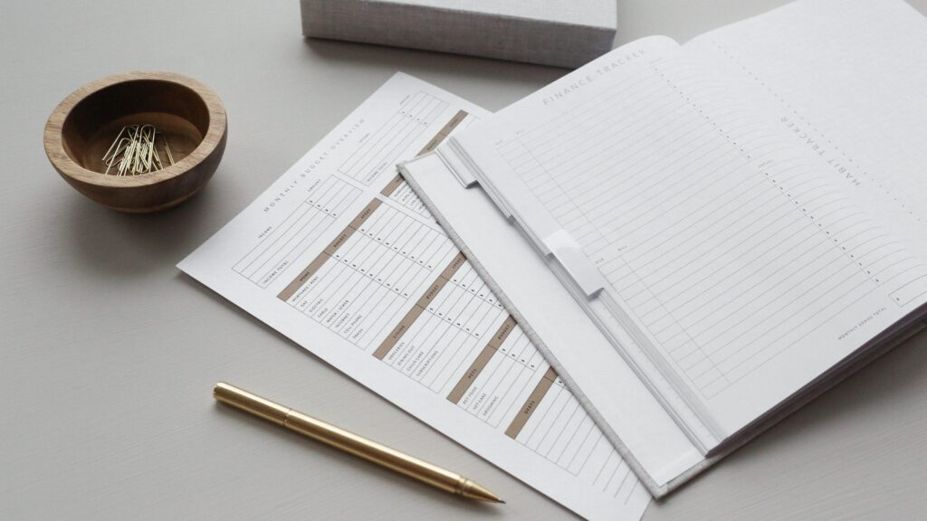 A financial tracker open on a table, with a pen and a pot of paperclips