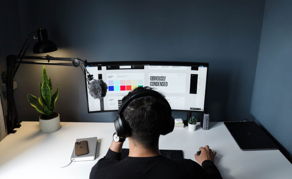 A behind view of a man working on graphic design on a computer. He is wearing a headset and has a microphone beside him.
