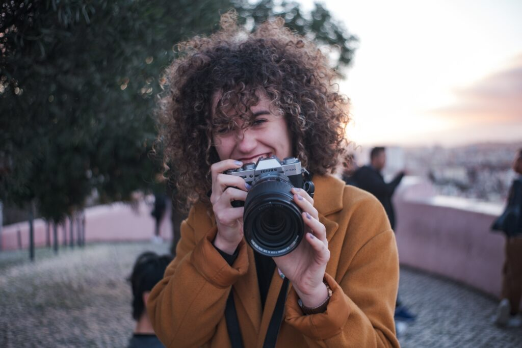 A woman holding a camera and smiling.